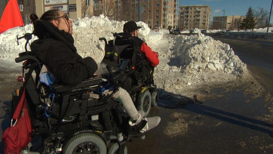 Deux personnes en fauteuil roulant électrique se dirigent vers un trottoir enneigé de Gatineau.