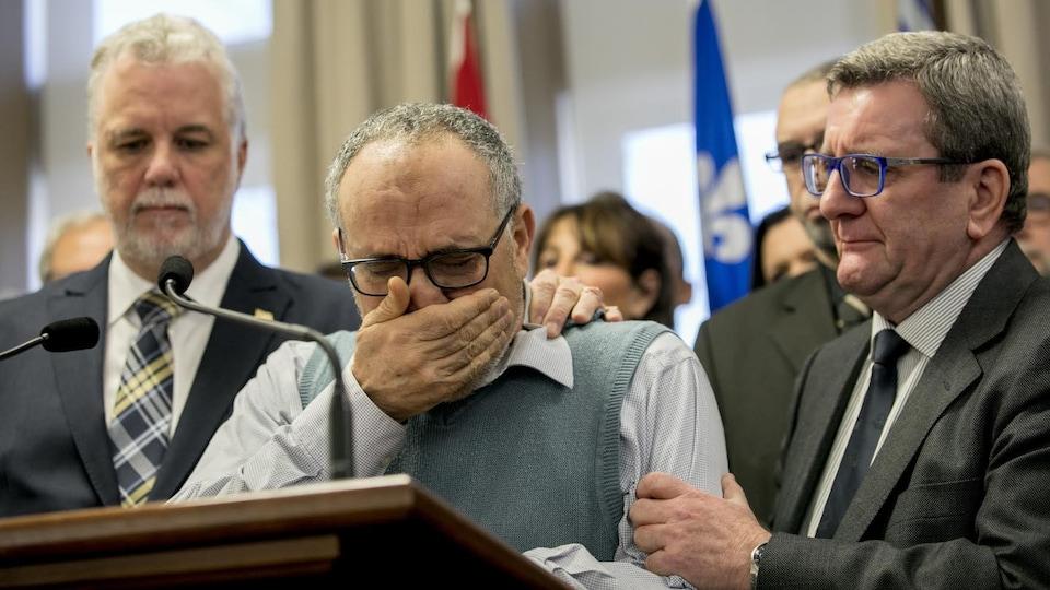Philippe Couillard et Régis Labeaume réconfortent Mohamed Labidi, en pleurs, lors d'une conférence de presse.