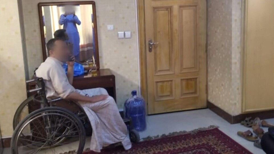 Un homme en fauteuil roulant au téléphone.