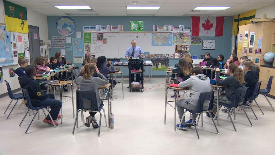 Une vingtaine d'élèves sont assis en classe devant leur professeur de français