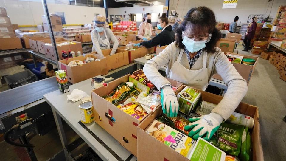 Une bénévole prépare une boîte de denrées alimentaires.