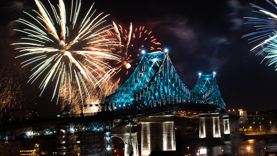 Une photo montrant le pont Jacques-Cartier illuminé en turquoise pendant que des feux d'artifice explosent en arrière-plan.