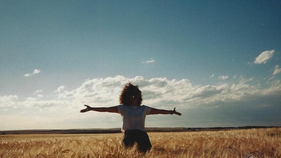 Une femme apprécie le moment présent debout au milieu de champs de blé.