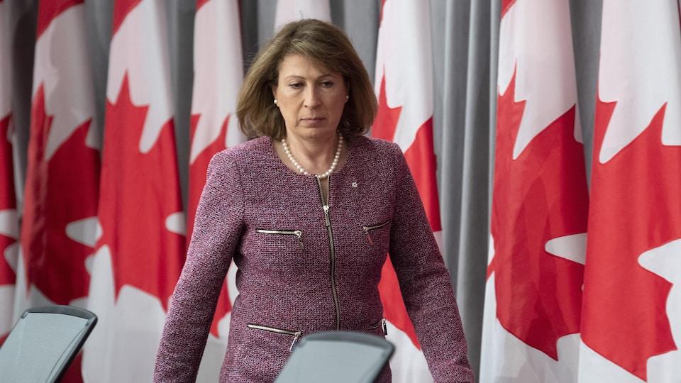 Mona Nemer marche devant des drapeaux du Canada.