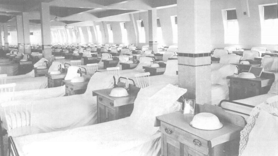 Des lits à une place et des tables de chevet sont alignés dans une immense pièce.