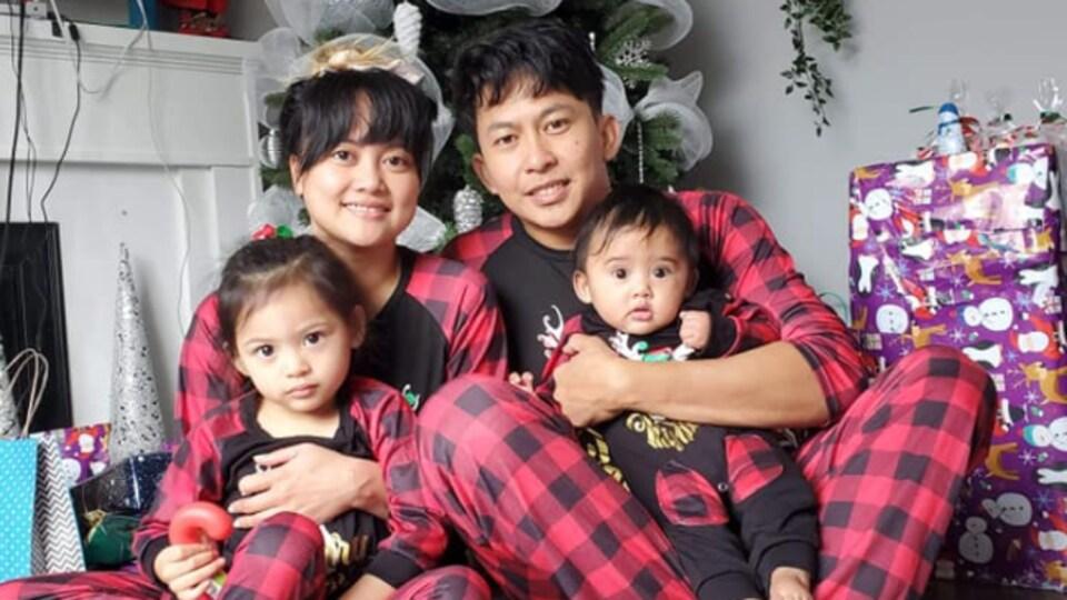 Les parents assis devant un sapin de Noël tiennent leurs deux enfants dans leurs bras.
