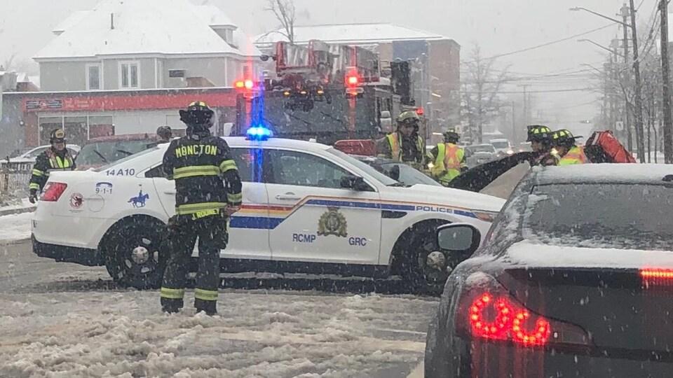 Des pompiers et des policiers examinent une voiture endommagée.