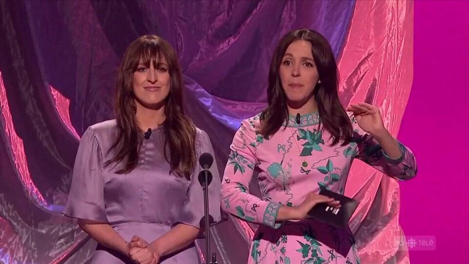 Deux comédiennes en robes couleur pastel parlent sur une scène devant le public.