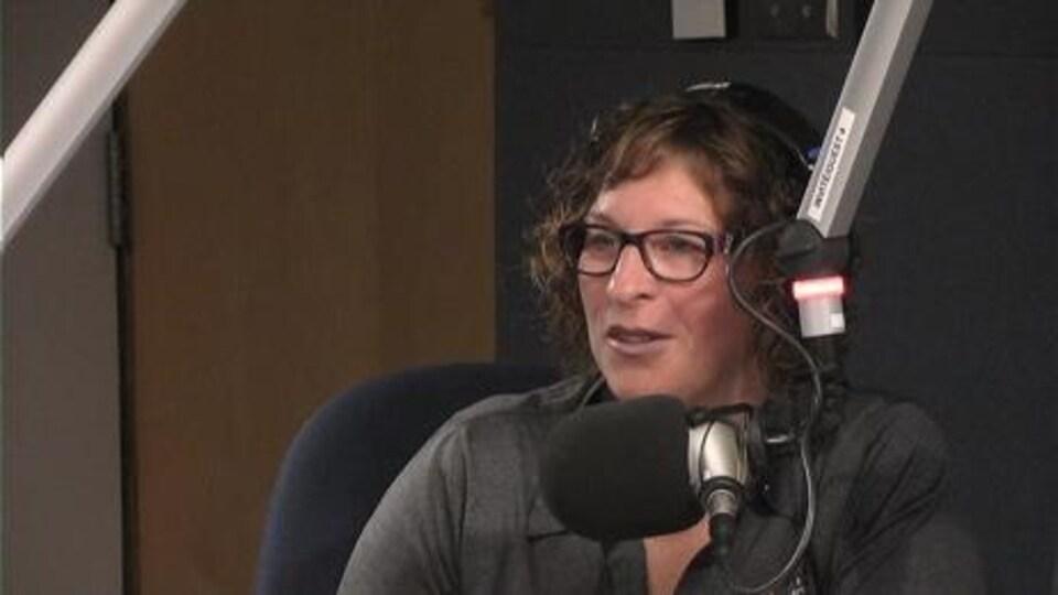 Monique Lacoste dans un studio radio parle au micro
