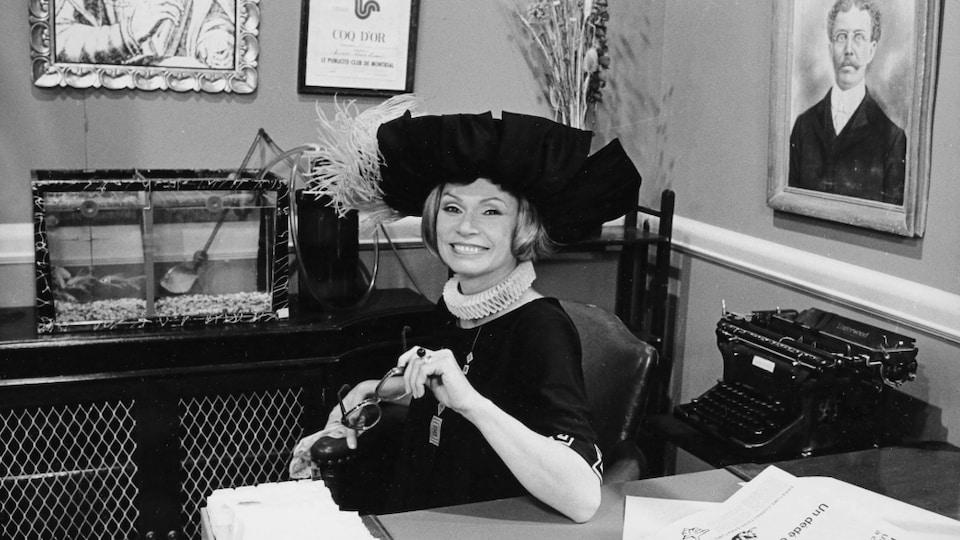 Monique Mercure, dans un costume des années 1920, est assise à un bureau, souriante.