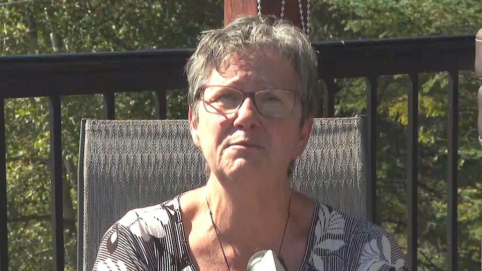 Une femme assise à l'extérieur devant un micro de Radio-Canada.