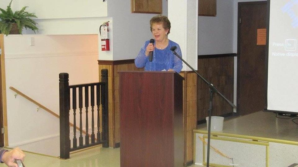 Une femme derrière un podium, à côté d'une scène, tient un micro.