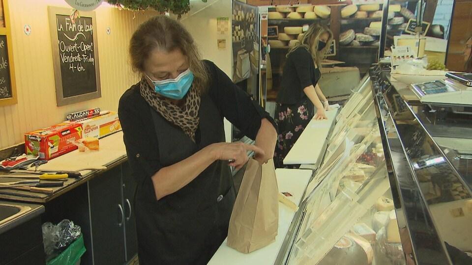 Une femme masquée derrière un étal de marché dépose des achats dans un sac en papier.