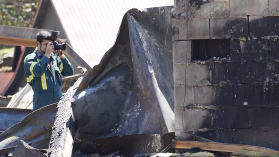 Un homme prend des photos de l'immeuble ravagé par les flammes.