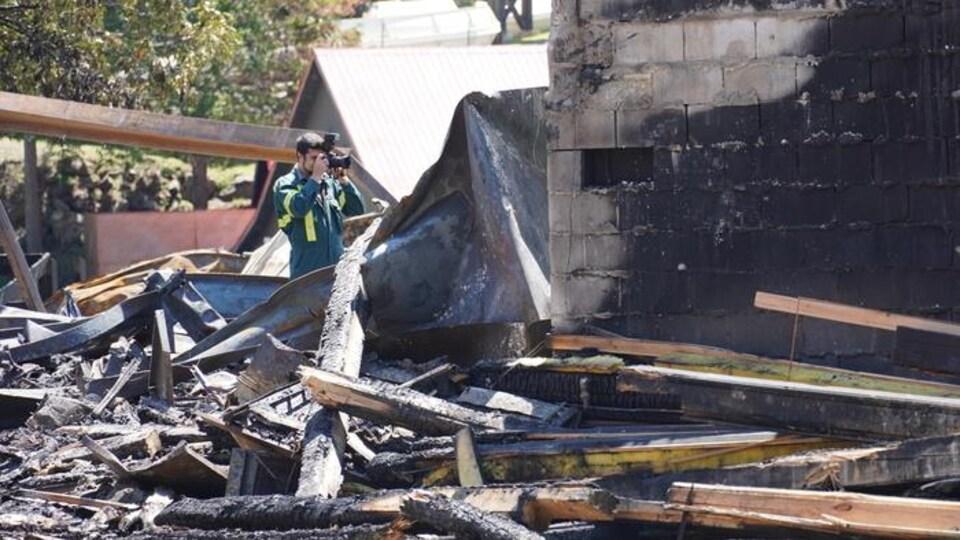 Un homme prend des photos de dommages laissés après un incendie.