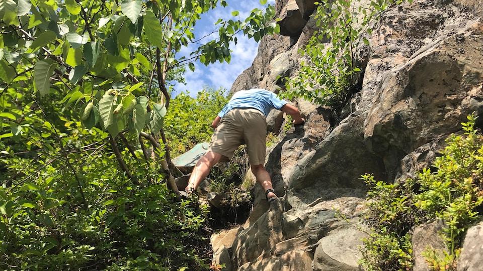 Un homme escalade une paroi rocheuse.