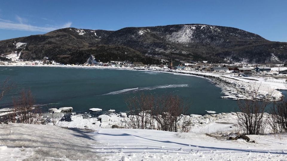 Vue de Saint-Maxime-du-Mont-Louis en hiver. De la neige recouvre le village, situé devant une anse.