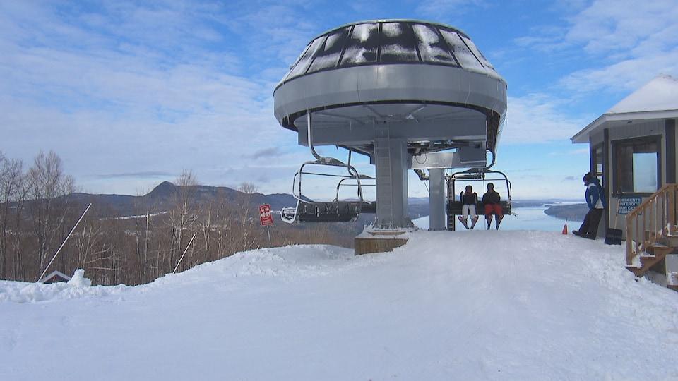 Deux skieurs sont dans une remontée mécanique. Ils arrivent au sommet de la montagne. Derrière, on aperçoit un lac.