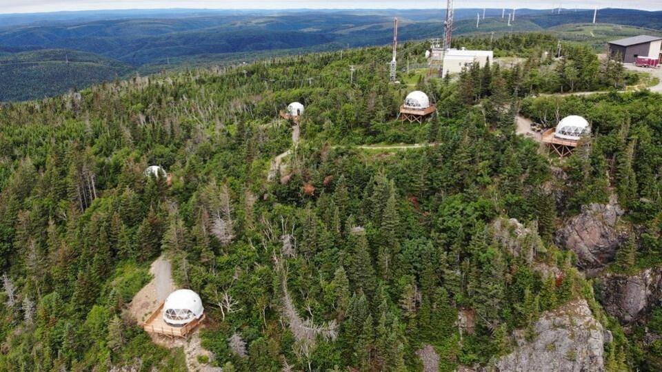 Vue aérienne des cinq tentes sphériques installées sur des plateformes au sommet d'une montagne.