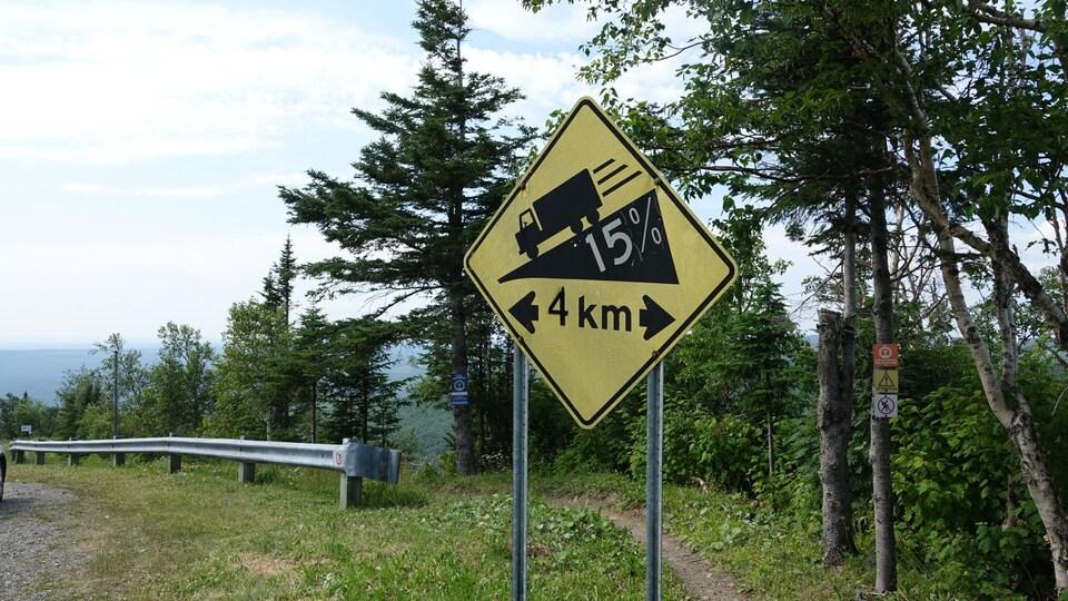 Une pancarte avec un pictogramme de camion qui dévale une pente de 15 % d'inclinaison.