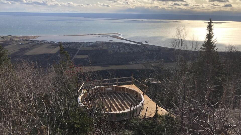 Une plateforme de bois à flanc de montagne surplombe la baie des Chaleurs