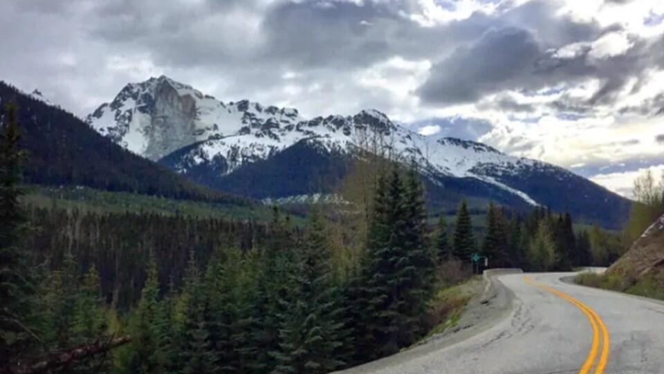 À droit une route déserte. À gauche une forêt qui mène à une montagne où une partie du sommet est détruit.