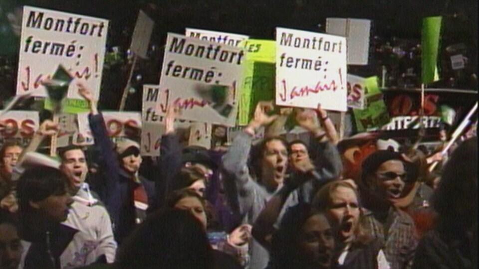 Des manifestants hurlant et brandissant des panneaux
