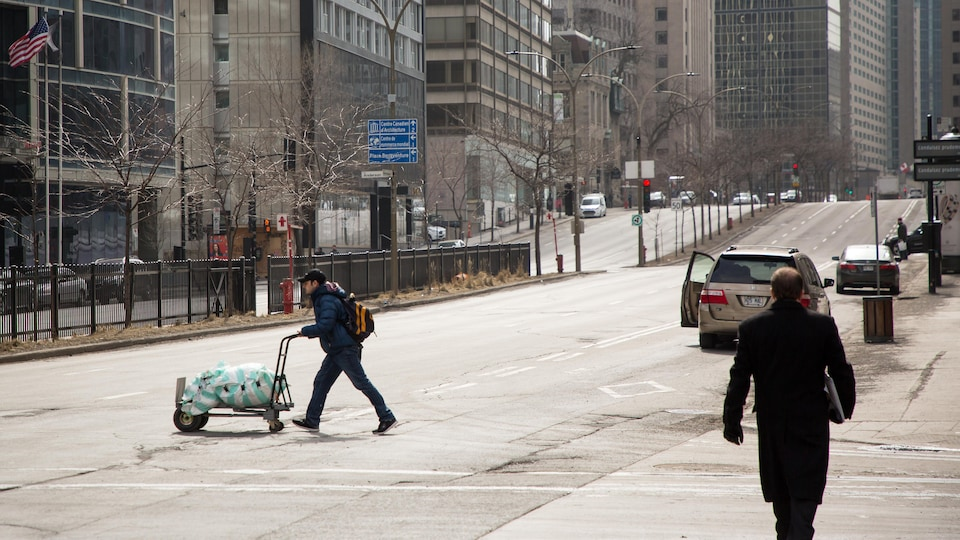 Un homme traverse la rue en poussant un chariot de marchandise.