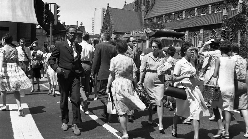 Des passants traversent l'intersection achalandée des rues Sainte-Catherine et Université, à Montréal, en 1963.
