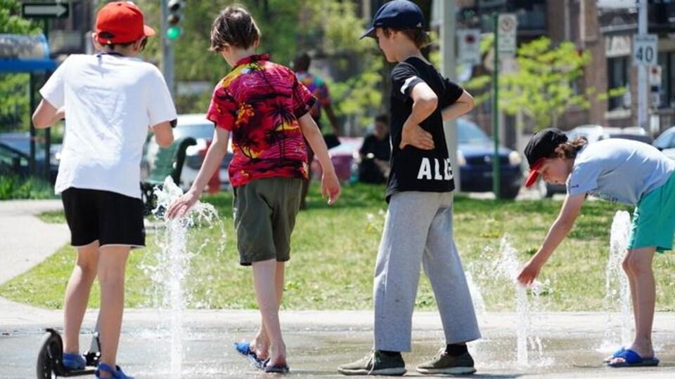 De jeunes garçons s'amusent dans un parc près d'un jeu d'eau.