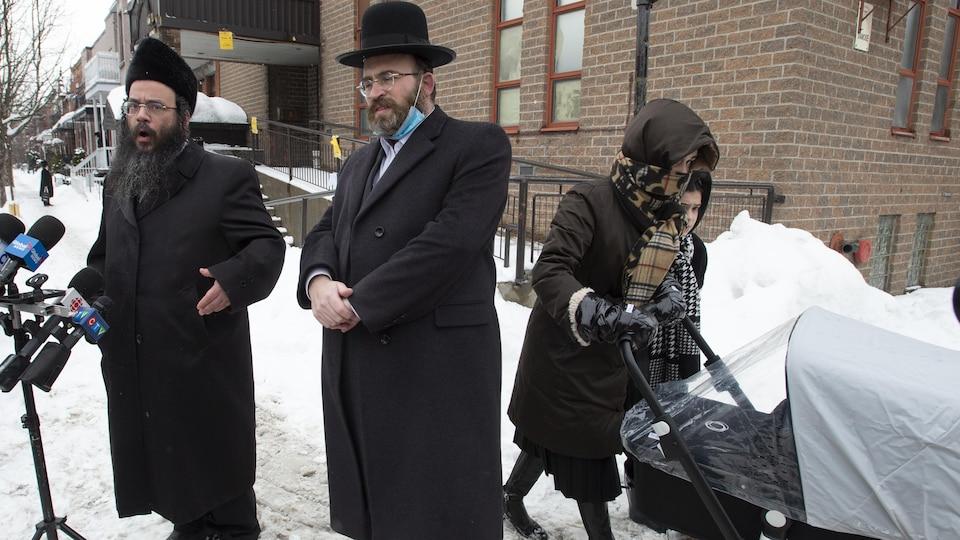 Abraham Ekstein et Max Lieberman du Conseil des juifs hassidiques du Québec s'adressent à des journalistes pendant qu'une mère passe avec ses enfants dans une rue du quartier Outremont, à Montréal.