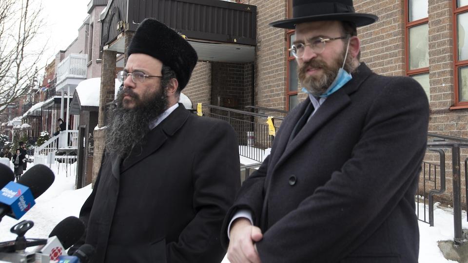 Deux hommes du Conseil des juifs hassidiques du Québec sur un trottoir de Montréal en hiver.