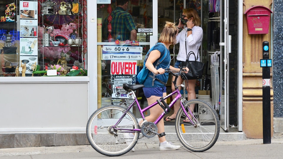 Des clients, dont une cycliste, à l'entrée d'un commerce.