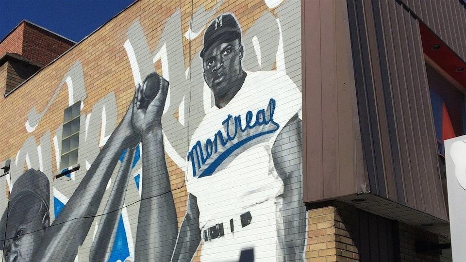Une murale représentant un joueur de baseball noir sur un mur de briques