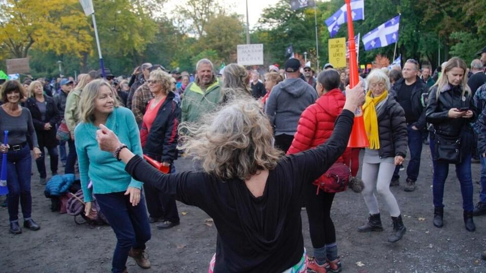 Des dizaines de personnes sans masques sont réunies et se tiennent à moins de deux mètres l'une de l'autre.