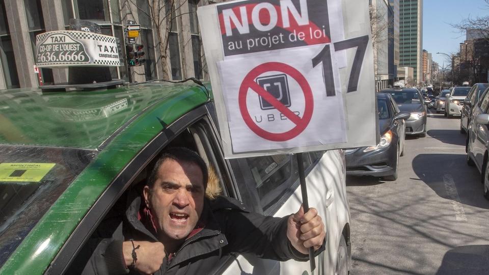 Assis dans son véhicule, un conducteur de taxi brandit une pancarte où il est écrit « Non au projet de loi 17 ». Derrière lui, d'autres taxis font la file dans les rues de Montréal.