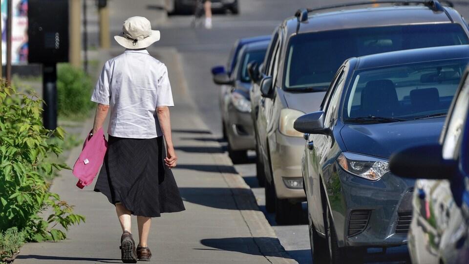 Une femme âgée, qu'on voit de dos, marche sur un trottoir de Montréal.