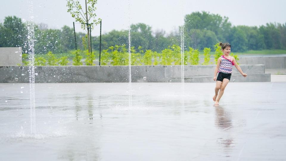 Une fillette profite des jeux d'eau de la plage de l'Est de Montréal.