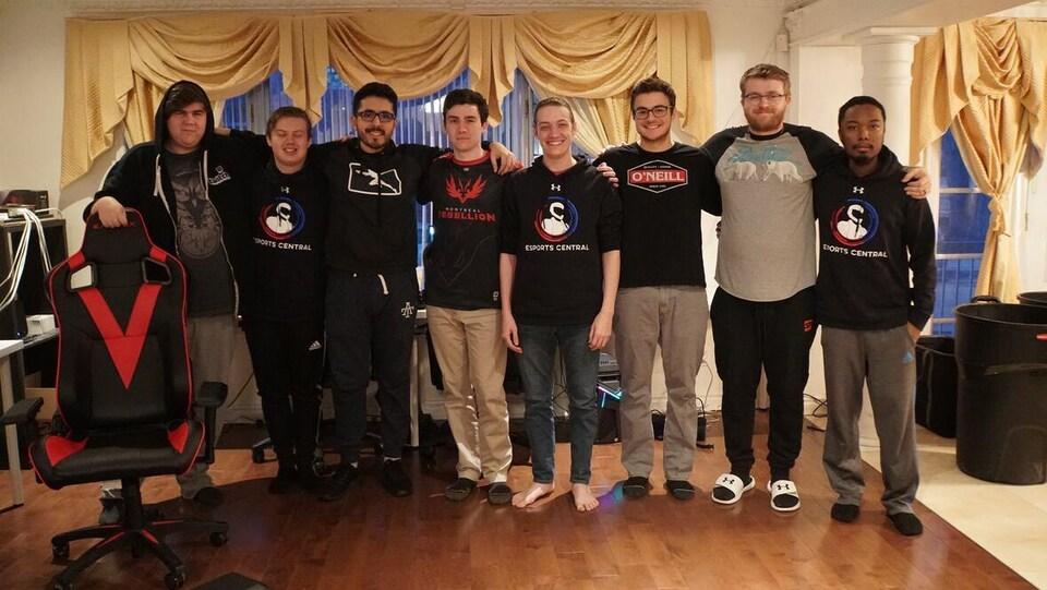 Une photo montrant huit jeunes hommes bras dessus, bras dessous dans le salon d'une maison.