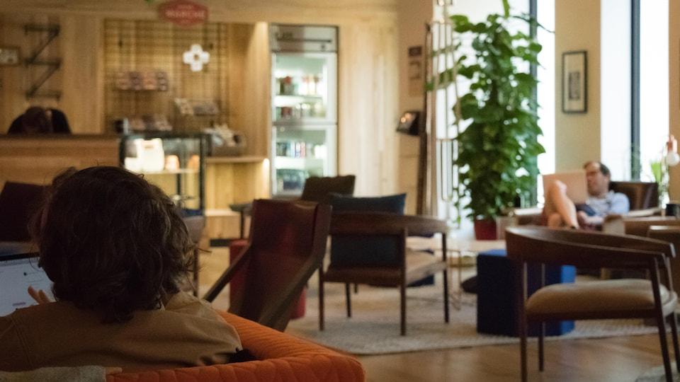 Une photo montrant l'espace café des bureaux d'Erudite AI, où l'on peut voir des personnes assises dans des fauteuils en train de travailler sur des ordinateurs portables.