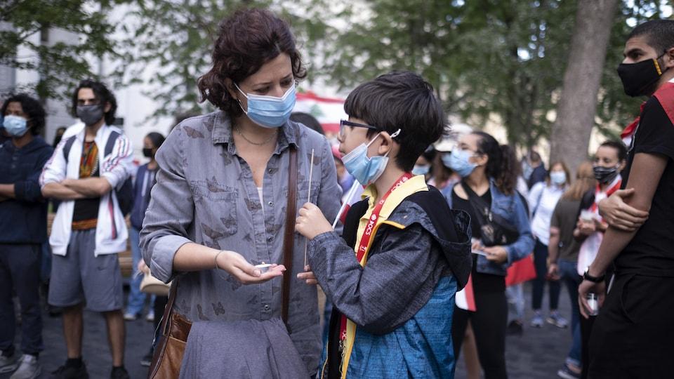 Une participante tenant une bougie avec un petit garçon.