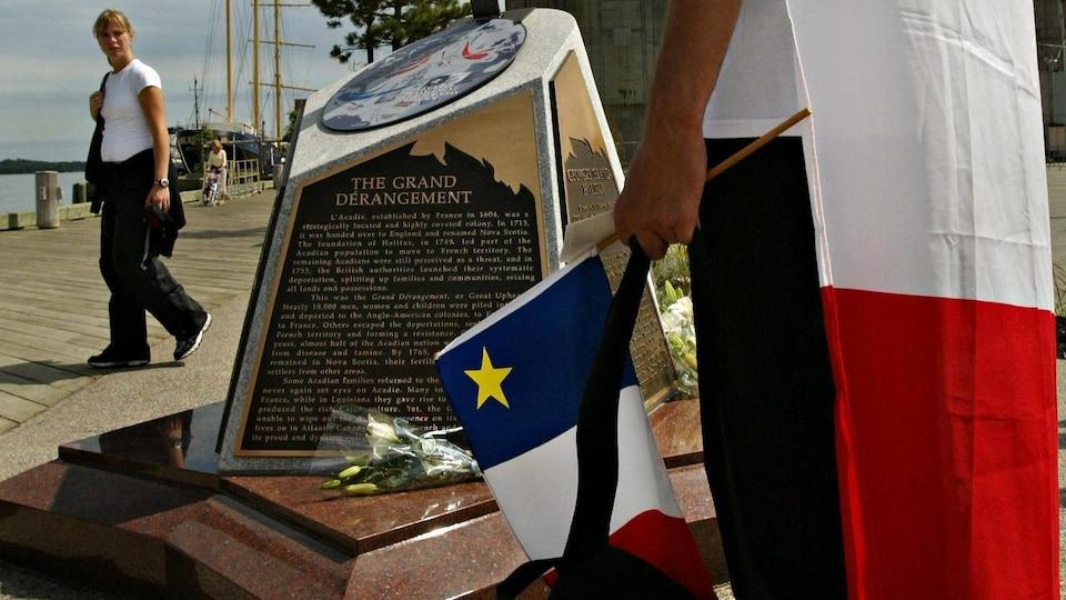 Douglas Lapierre, vêtu d'un drapeau acadien, observe le monument commémorant le Grand Dérangement.