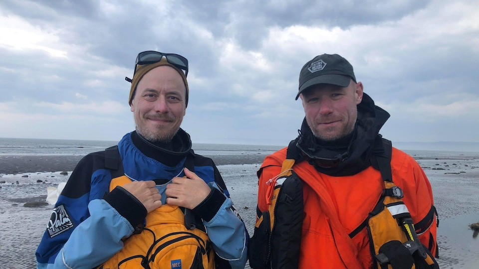 Justin Roy et Nicolas Roy sont habillés avec plusieurs épaisseurs de combinaison qui vont dans l'eau. Ils sourient à la caméra et se trouvent sur la plage.
