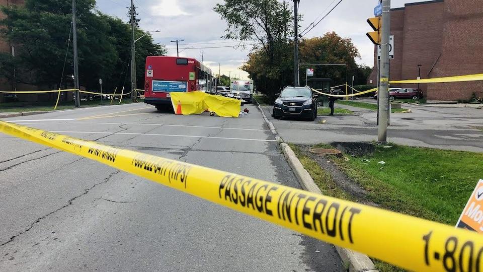 Un autobus, des ambulances et un périmètre de sécurité entourant les lieux d'un accident.