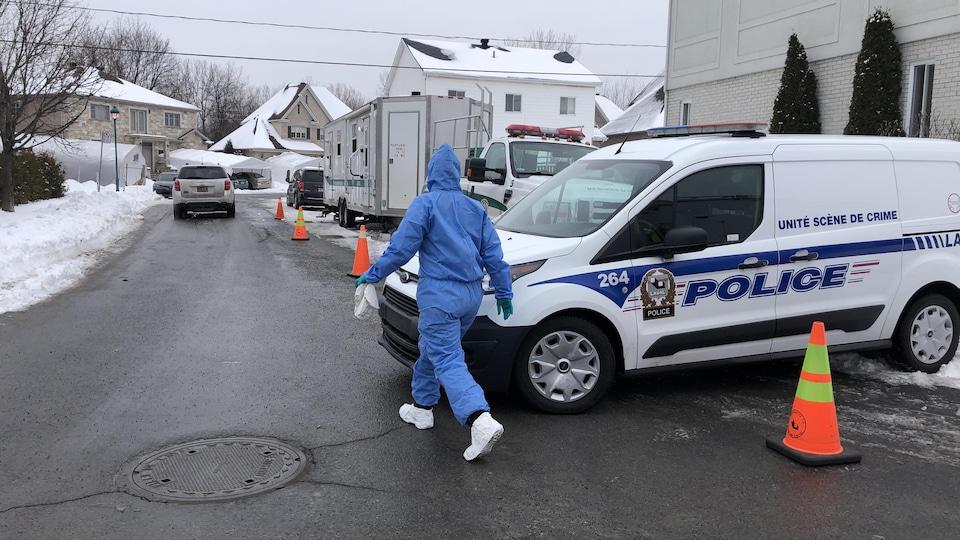 Plusieurs véhicules de police sont stationnés autour de la maison.