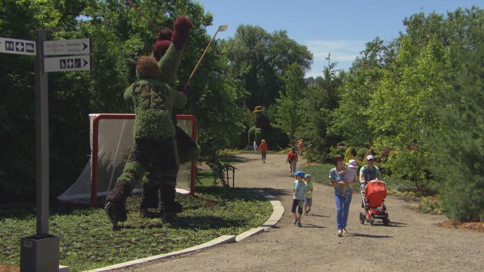 Des marcheurs sur un sentier qui admirent des sculptures horticoles.