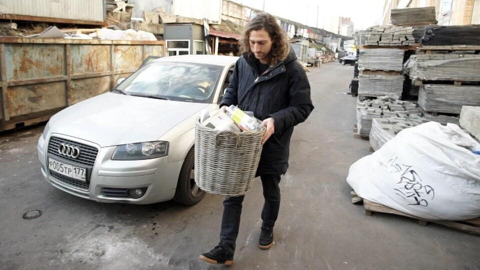 Un homme tient une poubelle dans ses mains.