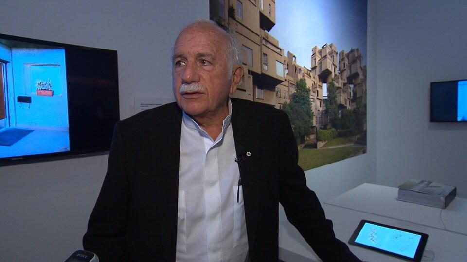 L'architecte Moshe Safdie, dans le décor d'une exposition réalisée sur son oeuvre Habitat 67, dont on voit une photo derrière lui.