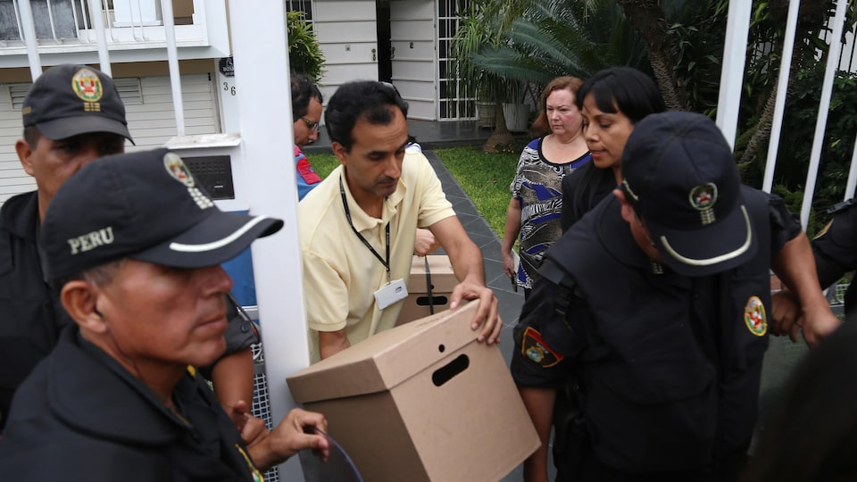 Un homme, entouré de policiers, sort une boîte de documents des bureaux de Mossack Fonseca