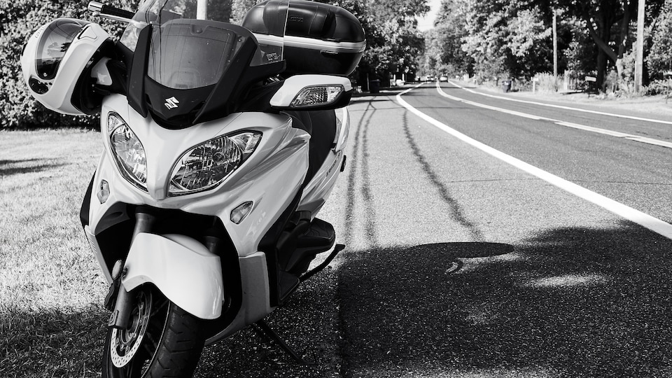 La moto est garée au bord de la route.